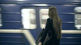Flickatonåringen som väntar på gångtunneldrevet, väntar och kommer ombord arkivfilmer