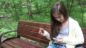 Flickatonåringsammanträde på en bänk i parkera Använder telefonen och att äta en smörgås stock video