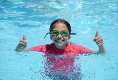 Flickatummar upp med skyddsglasögon i pöl Royaltyfri Foto