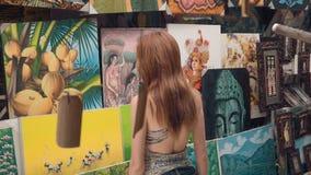 Flickaturist på den Sanur Bali konstmarknaden stock video