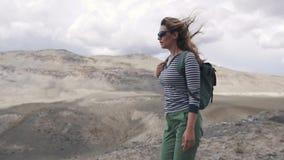 Flickaturisten går på en bergig terräng stående av handelsresanden kvinnafotvandrare med ryggsäcken, berg i arkivfilmer