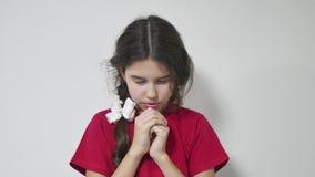 Flickaunge som ber på en vit bakgrund tonårig religion för flicka stock video