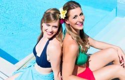 Flickavänner som garvar på simbassängen Royaltyfri Foto