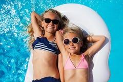 Flickavänner som tycker om sommar i simbassäng arkivbilder