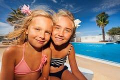 Flickavänner som tycker om sommar på simbassängen Arkivbild