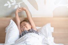 Flickavaker upp och sträcka på säng i morgon royaltyfri fotografi