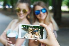 Flickavänner som utomhus tar foto med smartphonen Royaltyfri Bild