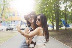 Flickavänner som utomhus tar selfiefoto med smartphonen Royaltyfri Fotografi