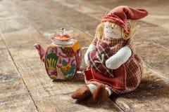 Flickenpuppen und Tee auf einem Holztisch Lizenzfreies Stockfoto