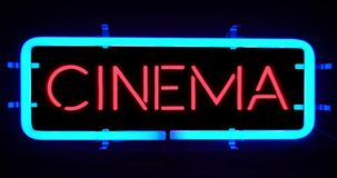 Flickering blinking blue neon sign on black background, cinema movie film entertainment sign stock footage