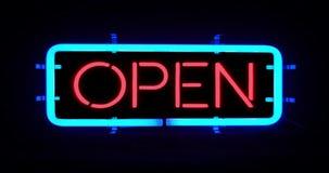Flickering blinking blue neon sign on black background, open shop bar sign