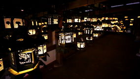 Flickering lanterns hang in a dark room inside Kasuga Taisha, Nara, Japan stock video