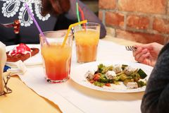 Flickor äter grekisk sallad i en restaurang och drinkcoctailar arkivfoton