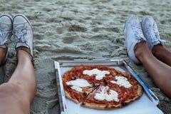 Flickor äter pizza på stranden, en matställe på solnedgången, påklädden för flickan äter fashionably pizza, arkivfoto