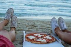 Flickor äter pizza på stranden, en matställe på solnedgången, påklädden för flickan äter fashionably pizza, royaltyfri fotografi