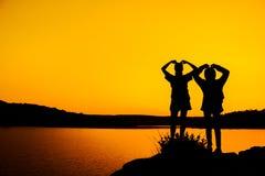 Flickor för kontur två sammanfogar händer för att fira framgången Royaltyfri Bild
