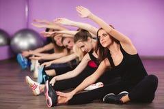Flickor för utbildning på kondition i idrottshallen arkivfoto