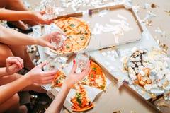 Flickor festar beröm som äter att dricka för pizza royaltyfria bilder