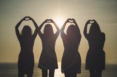 Flickor framme av solnedgången royaltyfri fotografi