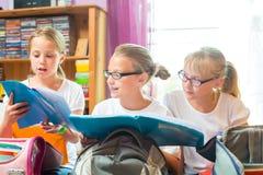 Flickor förbereder påsar för skola med böcker Fotografering för Bildbyråer