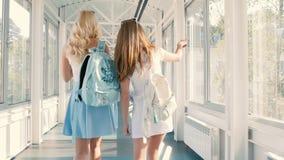 Flickor går över den långa korridoren stock video