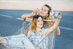 Flickor gör en sephi i ett lager, i en shoppingvagn arkivfoton