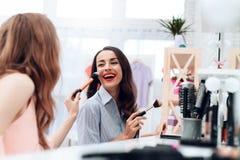 Flickor gör makeup i visningslokalen Två härliga flickor har gyckel och ler royaltyfri foto