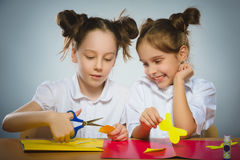 Flickor gör något från kulört pappers- användande lim och sax arkivbild