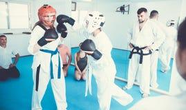 Flickor 20-26 gamla år munhuggas i par för att använda Taekwondo tech Arkivfoton