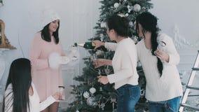Flickor hällde champagne nära en julgran stock video