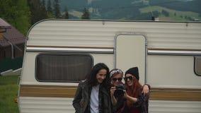 Flickor håller ögonen på foto nära husvagnen stock video