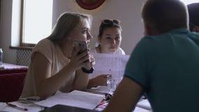 Flickor har diskussion med pojkar på tabellen i kafé arkivfilmer