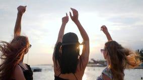Flickor har gyckel på invallningen, bästa flickvänner som dansar i solnedgången på stranden, tre kvinnliga lönelyftarmar upp på s lager videofilmer