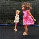 Flickor hoppar på en trampolin Arkivbild