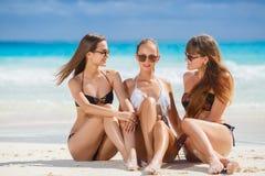 Flickor, i att solbada för bikinier som sitter på stranden Fotografering för Bildbyråer