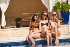 Flickor, i att solbada för bikinier som sitter på stranden Royaltyfri Foto