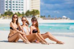 Flickor, i att solbada för bikinier som sitter på stranden Royaltyfria Bilder