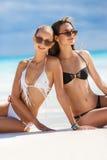Flickor, i att solbada för bikinier som sitter på stranden Royaltyfria Foton