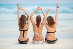 Flickor, i att solbada för bikinier som sitter på stranden Royaltyfri Bild