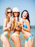 Flickor i bikini med glass på stranden Royaltyfria Foton