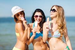 Flickor i bikini med glass på stranden Royaltyfria Bilder