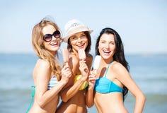 Flickor i bikini med glass på stranden Arkivfoto