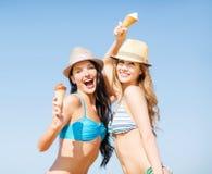 Flickor i bikini med glass på stranden Arkivbild