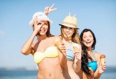 Flickor i bikini med glass på stranden Arkivbilder