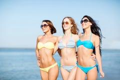 Flickor i bikini som går på stranden Royaltyfria Bilder