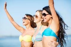 Flickor i bikini som går på stranden Arkivbild