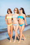 Flickor i bikini som går på stranden Arkivbilder