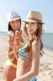 Flickor i bikinier med glass på stranden Royaltyfri Bild