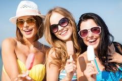 Flickor i bikinier med glass på stranden Royaltyfria Bilder