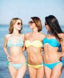 Flickor i bikinier som går på stranden Royaltyfri Fotografi